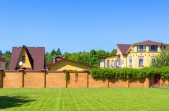 Beautiful country house with garage behind a brick fence. Summer stock photo