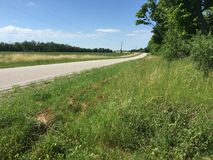 Country road in a nice peaceful area in Goderich Ontario Canada. A beautiful country road in a nice peaceful area in Goderich Ontario Canada, green grass and royalty free stock photography