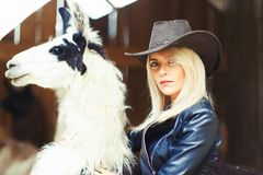 Beautiful country style blonde woman with a white lama Royalty Free Stock Images