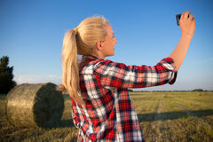 Beautiful country woman making selfie photo on smartphone in fie Stock Photos