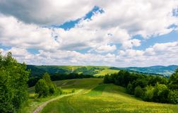 Beautiful countryside of Carpathians in summer. Country road through rural fields leads in to the forest. landscape with rolling hills under the cloudy sky stock photo