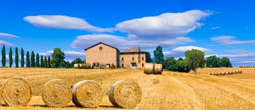 Beautiful countryside landscape with hay rolls and farm houses i Royalty Free Stock Image