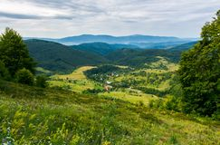 Beautiful countryside landscape in mountains. Forested hills and village down in the valley. overcast summer landscape royalty free stock images