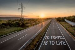 Beautiful Motorway with a Single Car at sunset with motivational message To Travel Is To Live. Beautiful Countryside Motorway with a Single Car at sunset with royalty free stock photo
