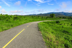 Beautiful countryside road in green field under blue sky Royalty Free Stock Photos