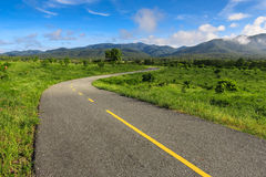 Beautiful countryside road in green field under blue sky Stock Photo