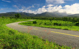 Beautiful countryside road in green field under blue sky Royalty Free Stock Images