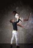 Beautiful couple in the active ballroom dance. On dark background Stock Photography
