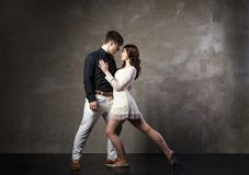 Beautiful couple in the active ballroom dance. On dark background Royalty Free Stock Photo