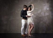 Beautiful couple in the active ballroom dance. On dark background Stock Photos