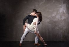 Beautiful couple in the active ballroom dance. On dark background Royalty Free Stock Photos