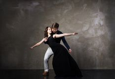 Beautiful couple in the active ballroom dance. On dark background Stock Image