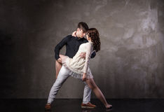 Beautiful couple in the active ballroom dance. On dark background Royalty Free Stock Images