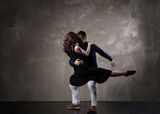 Beautiful couple in the active ballroom dance. On dark background Royalty Free Stock Image
