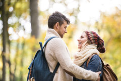 Beautiful couple in autumn nature against colorful autumn forest. Hugging Stock Photography