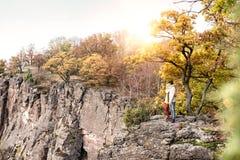 Beautiful couple in autumn nature against colorful autumn forest. Beautiful couple in autumn nature standing on a rock against colorful autumn forest Stock Photos