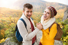 Beautiful couple in autumn nature against colorful autumn forest. Beautiful couple in autumn nature standing on a rock against colorful autumn forest, holding Stock Photo