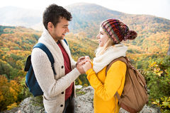 Beautiful couple in autumn nature against colorful autumn forest. Beautiful couple in autumn nature standing on a rock against colorful autumn forest, holding Royalty Free Stock Photo