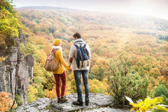 Beautiful couple in autumn nature against colorful autumn forest. Beautiful couple in autumn nature standing on a rock against colorful autumn forest, rear view Royalty Free Stock Image