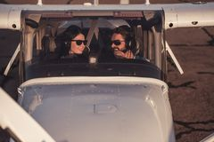 Couple in aircraft. Beautiful couple in aviation headsets is looking at each other and smiling while sitting in aircraft ready to fly Stock Photo