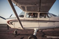 Couple in aircraft. Beautiful couple in aviation headsets is sitting in aircraft ready to fly Stock Images