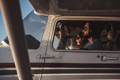 Couple in aircraft. Beautiful couple in aviation headsets is sitting in aircraft ready to fly Stock Photography