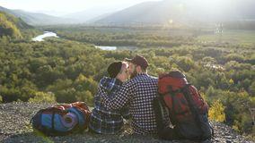 Beautiful couple sitting on the ground in the mountain. Beautiful couple with backpack sitting on the ground in the mountain on the forest background. Dolly stock footage