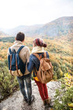 Beautiful couple with backpacks against colorful autumn forest. Beautiful couple with backpacks standing on a rock against colorful autumn forest, rear view Royalty Free Stock Photos