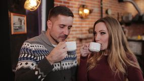 Beautiful couple at the bar in a cafe drinking coffee and talking. Young couple with smartphone talking and drinking drinking coffee in a cafe stock video footage