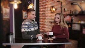 Beautiful couple at the bar in a cafe drinking coffee and talking. Young couple with smartphone talking and drinking drinking coffee in a cafe stock video
