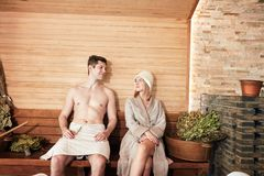 Beautiful couple relaxing in sauna and caring about health and skin. Beautiful couple in bathwear, relaxing in sauna and caring about health and skin, getting royalty free stock photos