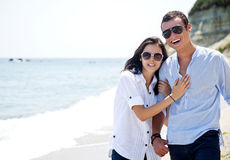 Beautiful couple beach. Young couple with sunglasses hugging and walking along beach Royalty Free Stock Image