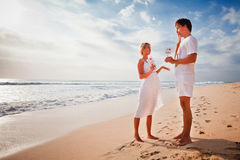 Beautiful couple on the beach are holding frame with signs of love and heart Stock Photography