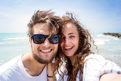 Beautiful couple on beach, laughing, taking selfie, smiling. Beautiful young couple on beach, smiling, taking selfie. Enjoying time at seaside Royalty Free Stock Photography