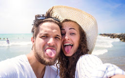 Beautiful couple on beach, laughing, taking selfie, sticking out. Beautiful young couple on beach, laughing, taking selfie, sticking out tongues. Enjoying time Stock Image