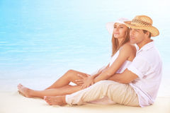 Beautiful couple on the beach. Sitting on the coast and hugging, enjoying peaceful sunny day on tropical resort, romantic summer vacation Royalty Free Stock Photo
