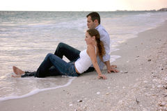 Beautiful couple at beach sitting in water clothed. A young couple on vacation are  at the beach sitting in the water, fully dressed as the sun begins to set Royalty Free Stock Photography