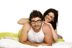 Beautiful couple in bed smiling at the camera Royalty Free Stock Images