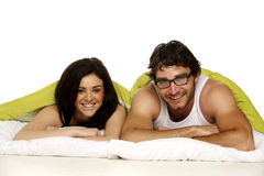 Beautiful couple in bed under a green duvet Royalty Free Stock Photo