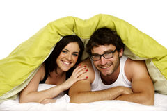 Beautiful couple in bed under a green duvet Royalty Free Stock Photos