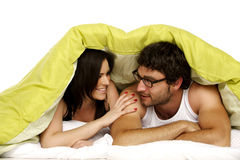 Beautiful couple in bed under a green duvet Stock Photos