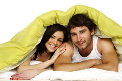 Beautiful couple in bed under a green duvet Royalty Free Stock Photography