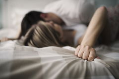 Beautiful couple being romantic and passionate in bed. Beautiful young couple being romantic and passionate in bed Stock Photos