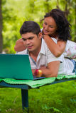 Beautiful couple on bench with laptop Stock Photo