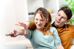 Beautiful couple bickering to change tv channel on remote contro Stock Photography