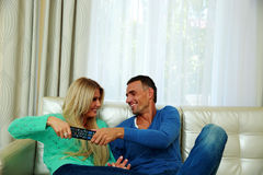 Beautiful couple bickering to change tv channel Stock Image