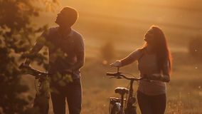 Beautiful couple with bikes on sunset. Happy young couple walking with bicycle in autumn park stock video footage