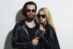 Beautiful couple in black leather wearing sunglasses and posing together Royalty Free Stock Photography