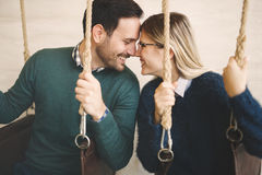 Beautiful couple bonding while in swing. Beautiful couple in love bonding while sitting in swing Royalty Free Stock Image