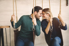 Beautiful couple bonding while in swing. Beautiful couple in love bonding while sitting in swing Stock Image